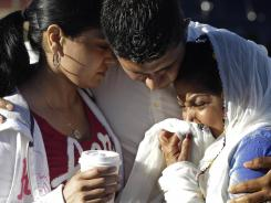 Amardeep Kaleka, son of the president of the Sikh temple, comforts members of the temple on Monday in Oak Creek, Wis. Satwant Kaleka, 65, founder and president of the temple, died in the shooting.