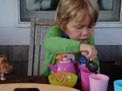 Rachel Eile, 3, enjoys some Cheerios cereal as part of her breakfast tea party.