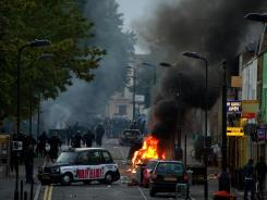 Riot police tackle a mob after a number of cars are set fire in Hackney, north London, Aug. 8, 2011.
