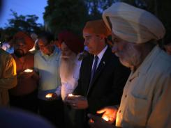 Wisconsin Gov. Scott Walker, along with members of the Sikh community, attends a candlelight vigil in Brookfield, Wis.