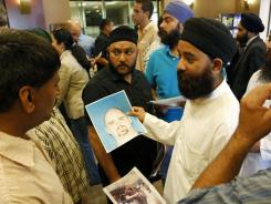 Members of the community hold up the mug shot of Wade Michael Page after a press conference at the Sikh Temple of Wisconsin.