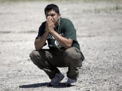 Amardeep Kaleka prays in a parking lot after the shooting at a Sikh temple in Oak Creek, Wis., Aug. 5.