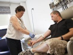 Retired Marine Matthew Pierce has his blood drawn by Margaret Ahlquist, a phlebotomist and medical technician, as part of a study in the Boston VA hospital. Troops who have been in direct combat in Iraq or Afghanistan, exposed to blasts and bullets, are living progressively more difficult lives physically and psychologically as veterans, according to the findings of an ongoing research project.