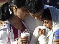 Amardeep Kaleka, son of the president of the Sikh Temple of Wisconsin, center, comforts others Monday in Oak Creek, Wis.