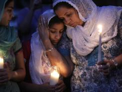 Worshipers in the Sikh community gather for a candle light vigil after prayer services at the Sikh Religious Society of Wisconsin, on Monday, in Brookfield, Wis.