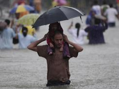 A man carries a girl on his shoulders as they cross a flooded area in Quezon City, north of Manila.