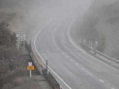 A cloud of ash hangs over State Highway 1 after the eruption of Mount Tongariro coated the area at Rangipo in the Tongariro National Park.