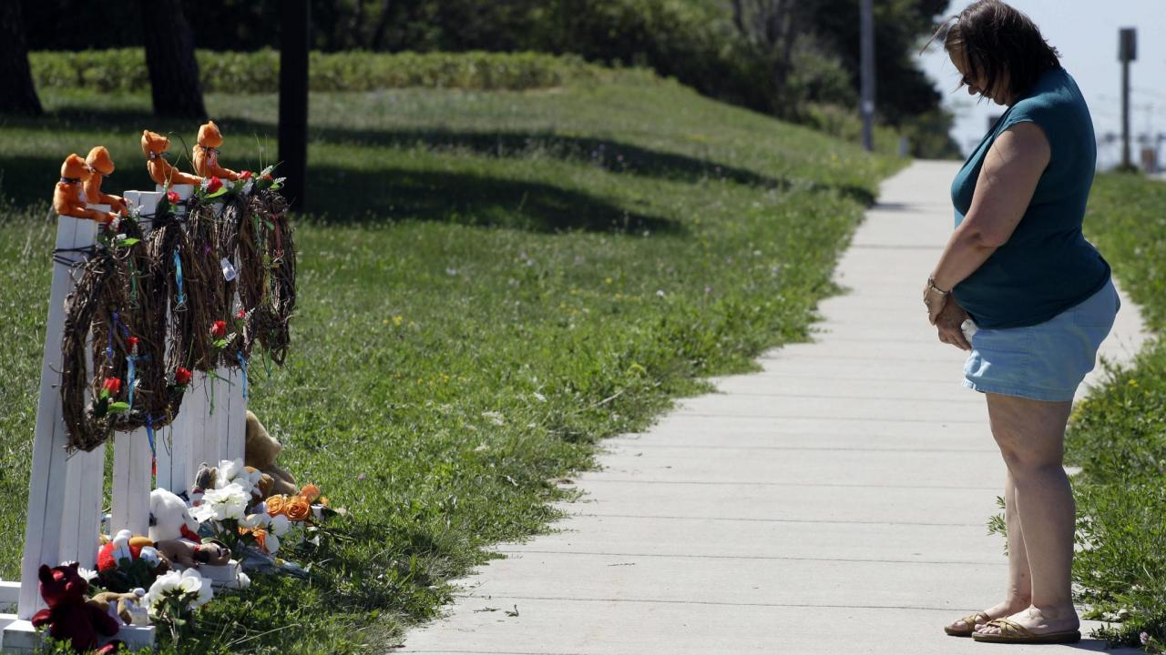 Peggy Renner-Howell pays her respects after laying flowers at a makeshift memorial near the Sikh Temple of Wisconsin on Tuesday.