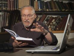 Menachem Cohen reads from a book at the library of Bar Ilan University, outside Tel Aviv, Israel.