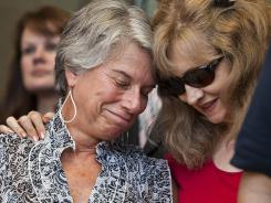 Tucson shooting victim Suzi Hileman, left, is hugged by Carol Dorushka, wife of shooting victim Kenneth Dorushka, at a news conference in Tucson on Tuesday.