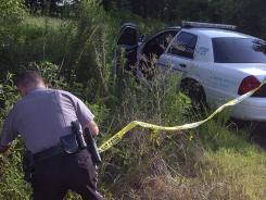"An Evangeline Parish sheriff's deputy tapes off a wooded area near Vidrine, La., where law enforcement officers were searching for the body of Michaela ""Mickey"" Shunick on Tuesday."