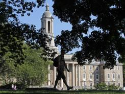 A Penn State University student walks across campus in July. A survey shows young people are concerned about how they will pay for college costs.