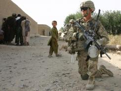 A U.S. soldier keeps watch while his colleagues speak to Afghans about the possible presence of Taliban in Nalgham village.