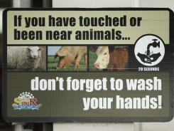 A sign warns people to wash their hands after being near farm animals at the Ohio State Fair on Aug. 1 in Columbus.