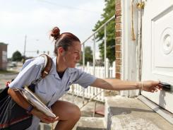 U.S. Postal Service letter carrier Monique Miller delivers mail in the Feltonville section of Philadelphia.