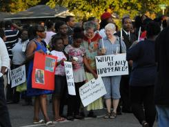 Supporters of Chavis Carter and his family, including Taelor Chavis, second from left, 9, and Kimi Miller, center, 9, hold signs during the candlelight vigil held in honor of Carter on Monday, Aug. 6, 2012, at the First Baptist Church on Kitchen Street in Jonesboro, Ark. (AP Photo/The Jonesboro Sun, Krystin McClellan) ORG XMIT: ARJON103