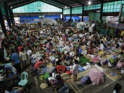 Flood victims stay inside a crowded basketball court converted into a temporary evacuation center in Quezon city on Thursday.