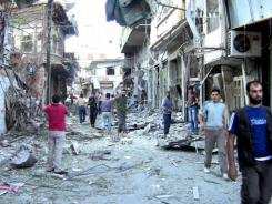 Syrians inspect damage caused by shelling by government forces in Damascus.