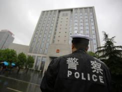 A police officer stands guard at the Hefei City Intermediate People's Court on Thursday in Hefei, China, where the murder trial of Gu Kailai is being held.