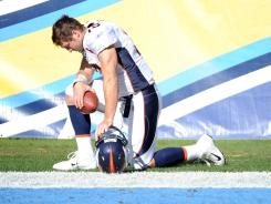 Tim Tebow, when he was with the Denver Broncos, prays before a game in November.