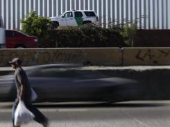 A Border Patrol agent drives his vehicle along the international border in Tijuana, Mexico.