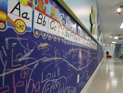 The walls of a learning center are decorated with examples of the alphabet and protected with chalk boards that children are encouraged to use.