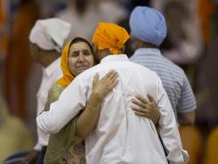 Mourners provide comfort at the funeral and memorial service for the six victims of the Sikh temple of Wisconsin mass shooting in Oak Creek, Wis.