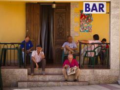 A group of men sit outside the only bar in Peleas de Abajo. The residents of this small village say they are ashamed of their status in Spain as the most indebted local government per capita in the country despite austerity measures and sales of assets.