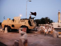 Egyptian soldiers stand on top of an armored personnel carrier at a military checkpoint in northern Sinai on Friday.