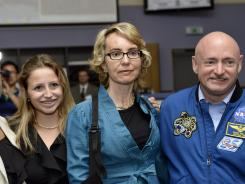 Former U.S. congresswoman Gabrielle Giffords, center, and her husband Mark Kelly pose for a picture July 25 in Meyrin, Switzerland, near Geneva.