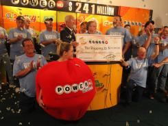 Co-workers claim the $241 million Powerball jackpot from the Iowa lottery office June 20 in Des Moines.