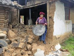 A villager walks in rubble outside her earthquake-damaged home in southwest China's Yunnan province county of Ninglang on June 25.