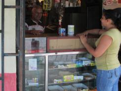 A shopper makes a purchase at a state-owned Mercal grocery store. The stores, founded by Venezuelan President Hugo Chavez, offer basic foodstuffs such as corn meal, sugar and meat, at heavily subsidized prices.