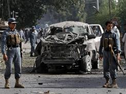 Afghan police officers inspect the wreckage of a vehicle after a bomb explosion in the city of Jalalabad, east of Kabul, on Monday.