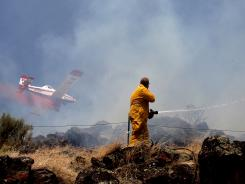 A member of the Rock Creek Rural Fire Protection District watches as a plane drops retardant on a fire south of Kimberly, Idaho, June 26.