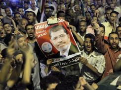Thousands of supporters raise a poster of Egypt's Islamist President Mohammed Morsi as they celebrate in Tahrir Square in Cairo on Sunday.