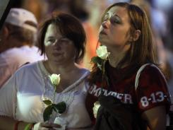 Tamiko Schaefer, of Melbourne, Fla., right, and Lacey Grabek, of Noblesville, Ind., reflect during a moment of silence for the seven people killed and dozens injured when stage rigging collapsed at the Indiana State Fair a year ago.