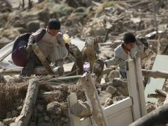 Two Iranian boys retrieve their belongings Sunday from ruins of their house after Saturday's earthquake in a village near the city of Varzaqan in northwestern Iran.