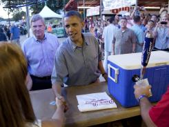 President Obama greets workers as he orders a beer at the Iowa State Fair on Monday in Des Moines.
