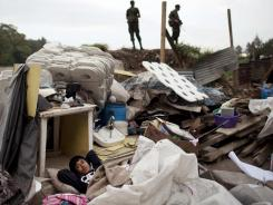 Marvin sleeps among his belongings as soldiers stand guard before police and army evicted residents of the Jacobo Arbenz settlement.