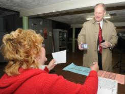 Rep. Mark Critz, D-Pa., shows his ID to an inspector as he prepares to vote in primary elections April 24 in Johnstown, Pa.