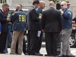 D.C. police and FBI agents gather outside the Family Research Council in Washington during an investigation into the shooting of a security guard at the lobbying group.