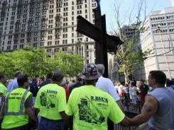 this July 2012 photo, World Trade Center construction workers hold hands during a prayer at a ceremony for the September 11 cross in New York.