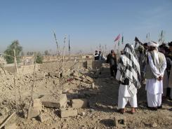 Afghan villagers look on at the site of a bomb blast in Lashkar Gah city, capital of Helmand province on Sunday. An IED explosion in the first hours of Eid-e Fitr, the end of the holy month of Ramadan, killed two and wounded 7 civilians at a graveyard in Helmand.