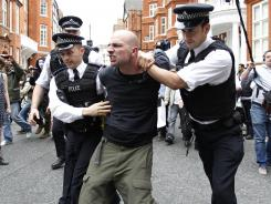 British police officers arrest a protester supporting WikiLeaks founder Julian Assange in front of the Ecuadorian Embassy in London on Thursday.