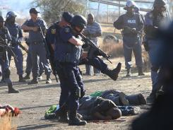 Police surround the bodies of striking miners after opening fire on a crowd at the Lonmin Platinum Mine near Rustenburg, South Africa on Thursday.