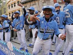 Members of the Little League team from Willemstad, Curacao, rides in the Little League Grand Slam Parade as it makes its way through downtown Williamsport, Pa., on Wednesday.