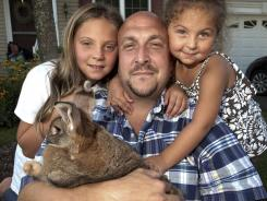 Lidsky, left, poses with her father Josh, and sister Madison, and Sandy, the family bunny, in North Haven, Conn.