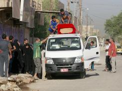 Relatives and friends of a man killed in a car bomb attack load his coffin onto a vehicle during his funeral in the Zafaraniyah neighborhood of Baghdad, Iraq on Friday.