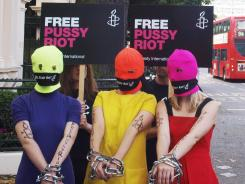 Three Amnesty International activists dressed as the Russian Band Pussy Riot protest for the release of three band members who were sentenced Friday for staging a protest stunt against President Putin.